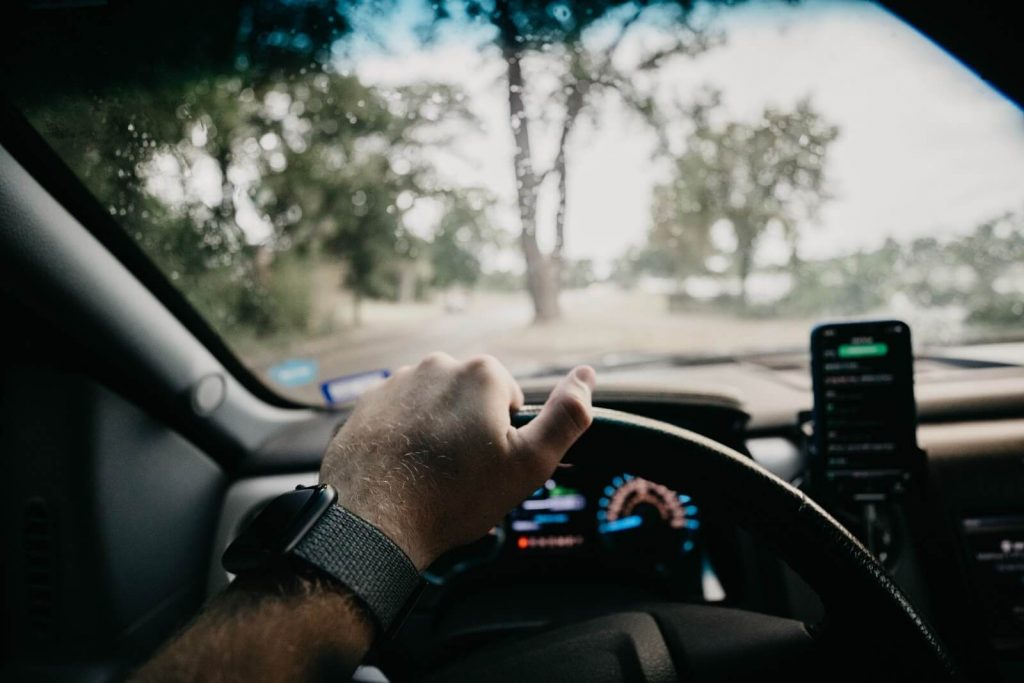 a man's hand on the steering wheel while driving